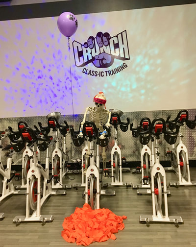 A skeleton in a disco-fan headband rides a spin bike at Crunch.